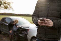 Man som kallar för att anmäla bilolycka på landsvägen arkivbilder