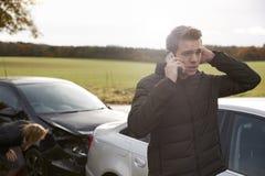 Man som kallar för att anmäla bilolycka på landsvägen arkivfoton