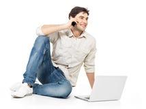 Man som kallar vid mobil med bärbar dator Royaltyfria Foton