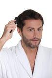 Man som kammar hår fotografering för bildbyråer