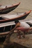 Man som kastar aska till Gangesen Arkivfoto