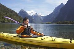 Man som Kayaking i berg sjön arkivbild