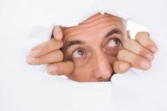 Man som kikar till och med sönderriven vit yttersida Fotografering för Bildbyråer