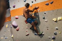 Man som klättrar den inomhus stenblockväggen fotografering för bildbyråer