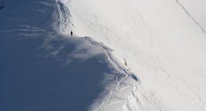 Man som klättrar det snöig berg Arkivfoto