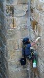 Man som klättrar en vägg arkivbild