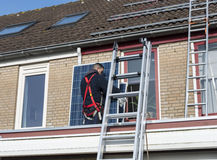 Man som klättrar stegen med solpanelen fotografering för bildbyråer