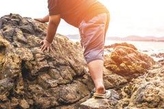 Man som klättrar stenen på stranden arkivbild