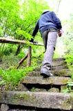 Man som klättrar trappa för en sten Arkivfoto