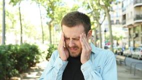 Man som klagar lida migrän i gatan arkivfilmer