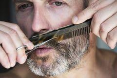 Man som klipper hans skägg Arkivfoto