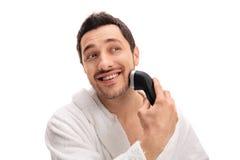Man som klipper hans skägg med en rakapparat Royaltyfria Bilder