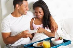 Man som kommer med kvinnafrukosten i säng på berömdag Royaltyfri Bild