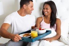 Man som kommer med kvinnafrukosten i säng på magasinet Arkivbild