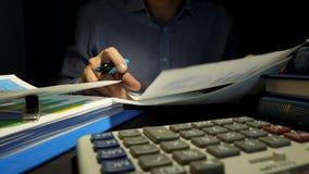 Man som kontrollerar den finansiella rapporten eller affärsdokument Revisor på arbetet arkivfilmer