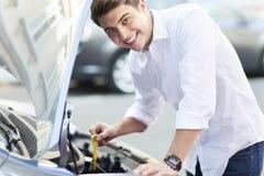 Man som kontrollerar den olje- nivån i bil Royaltyfri Foto