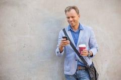 Man som kontrollerar hans telefon Fotografering för Bildbyråer