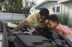 Man som kontrollerar motorn av bilen arkivfoton