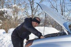 Man som kontrollerar motorn i det snöig vädret Royaltyfria Bilder