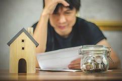 Man som kontrollerar räkningar och har finansiella problem med den hem- skulden, pengarbegrepp , köper fastigheten, en lägenhet royaltyfri foto