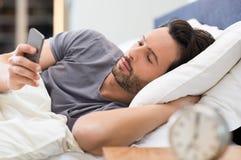Man som kontrollerar telefonen i säng royaltyfri foto