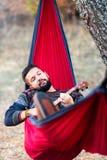 Man som kopplar av i en hängmatta på att fotvandra tur royaltyfri foto