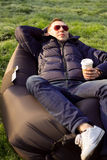 Man som kopplar av i en uppblåsbar soffa Fotografering för Bildbyråer