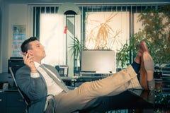 Man som kopplar av i hans kontor Arkivfoton