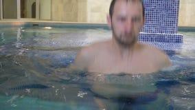 Man som kopplar av i simbassäng lager videofilmer