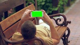 Man som kopplar av i sommarsolsken med hans mobil lager videofilmer