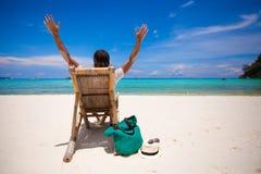 Man som kopplar av i trästolen på sandstranden Royaltyfria Foton