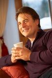 Man som kopplar av med den varma drinken på den hållande ögonen på TV:N för Sofa Royaltyfri Foto