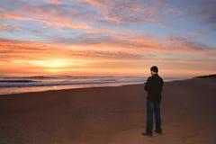 Man som kopplar av på stranden på soluppgång arkivfoton