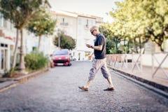 Man som korsar gatan som ser hans telefon royaltyfria bilder