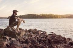 Man som kort efter förbiser en solnedgång för sjö Fotografering för Bildbyråer