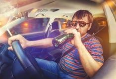 Man som kör bilen och dricker öl Arkivbild