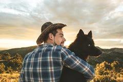 Man som kramar hans hund på solnedgången Begrepp av förälskelse mellan mannen och hunden royaltyfri fotografi