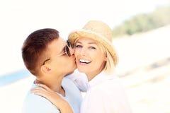 Man som kysser en kvinna på stranden Arkivfoton