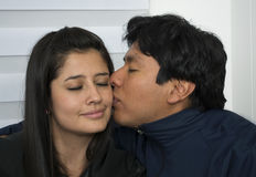 Man som kysser hans glade flickvän Fotografering för Bildbyråer