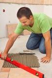 Man som lägger keramiska golvtegelplattor - kontrollera fodrar med en nivå Arkivfoton
