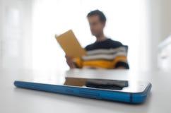 Man som läser en bok som lämnar smartphonen på tabellen royaltyfri bild