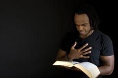 Man som läser en isolerad bibel på svart Royaltyfri Foto