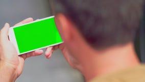 Man som läser ett textmeddelande på en mobil arkivfilmer