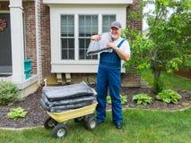 Man som lastar av påsar av komposttäckning från en skottkärra royaltyfria foton