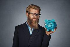 Man som ler bärande exponeringsglas för innehavspargris som både isoleras på grå färger royaltyfri foto