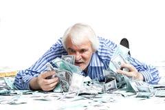 Man som ligger i pengarna Arkivfoto