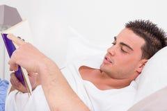 Man som ligger i sängläsebok royaltyfri bild
