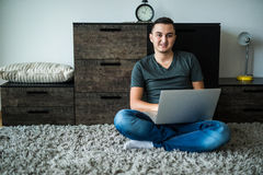 man som ligger på matta, medan genom att använda bärbara datorn arkivbild