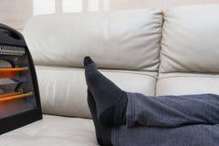 Man som ligger på soffan med värmeelementet nära hans fot arkivbild