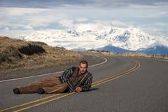 Man som ligger på vägen med berget bakom arkivfoto